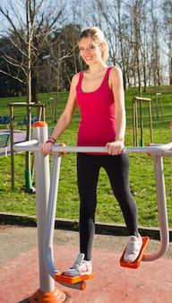 Retrato de mulher alegre em fitness wear exercitando com equipamentos no parque