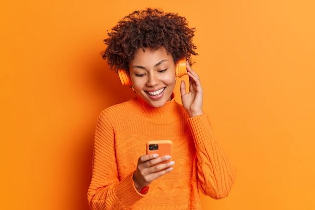 Retrato de mulher alegre escolhe música para ouvir em sua lista de reprodução goza de bom som em fones de ouvido concentrados na tela do smartphone vestida casualmente isolada sobre a parede laranja