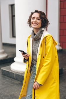 Retrato de mulher alegre feliz andando pela rua, falando em seu telefone celular, sendo satisfeito com boas notícias