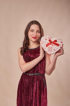 Retrato de mulher alegre no vestido vermelho, segurando a caixa de presente