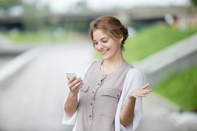 Retrato de mulher alegre olhando a tela do smartphone
