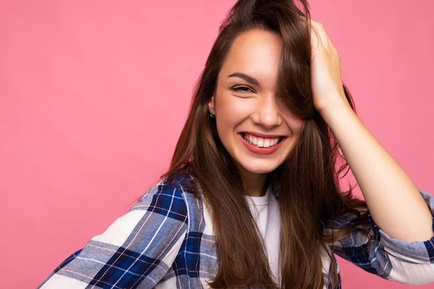 Retrato de mulher alegre positiva na moda em roupa hipster isolada em rosa