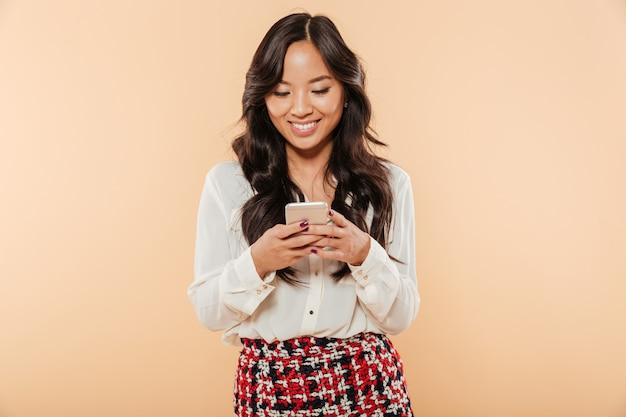 Retrato de mulher alegre rolagem feed ou leitura de mensagem de texto usando seu smartphone sobre fundo pêssego