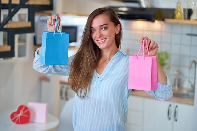 Retrato de mulher amada fofa feliz e sorridente satisfeita com uma bolsa de presentes colorida
