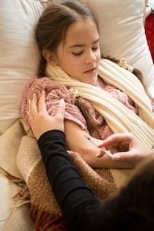 Retrato de mulher aplicando injeção nas mãos de meninas, deitada na cama