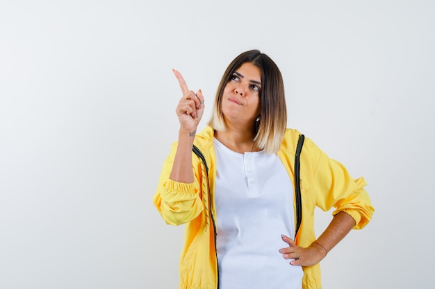 Retrato de mulher apontando para cima com camiseta, jaqueta e olhar esperançoso de frente
