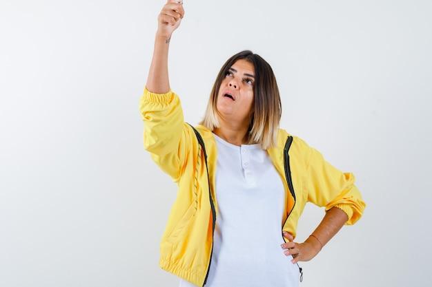 Retrato de mulher apontando para cima com camiseta, jaqueta e vista frontal focada