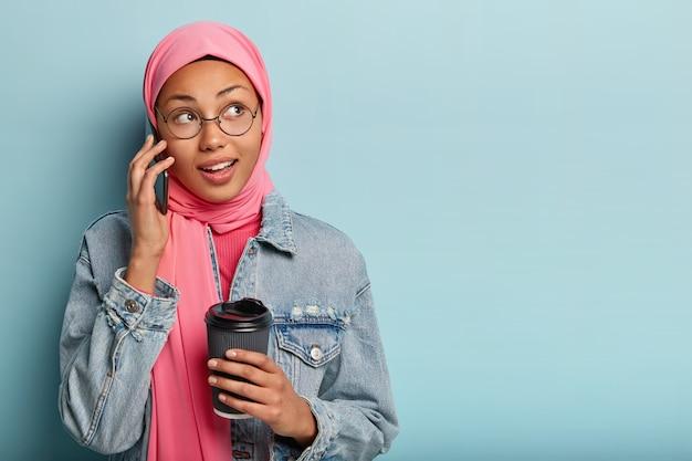 Retrato de mulher árabe encantada faz arranjos via celular, segura copo de papel com café, recebe boa oferta, olha de lado