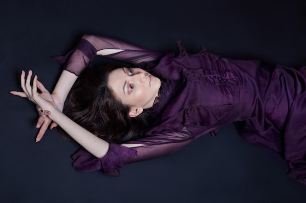 Retrato de mulher armênia moda contraste com grandes olhos azuis deitado no chão em um vestido roxo. linda garota linda posando em vestido de noite. maquiagem brilhante, mulher