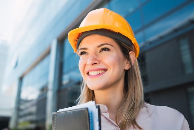 Retrato de mulher arquiteto profissional usando capacete amarelo e em pé ao ar livre. conceito de engenheiro e arquiteto.