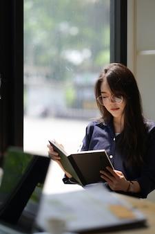 Retrato, de, mulher asian, lendo um livro, em, biblioteca
