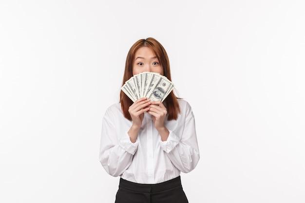 Retrato de mulher asiática animado e satisfeito ficou rico, contando o segredo da riqueza, escondendo o rosto atrás de dinheiro, segurando o leque de dinheiro e sorrindo com os olhos na câmera, suporte