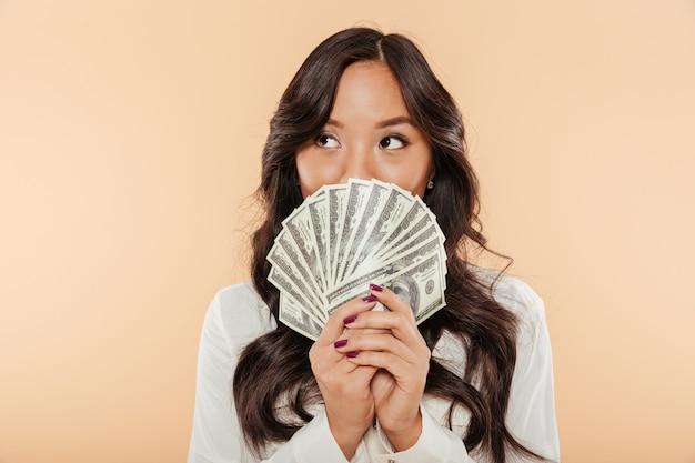 Retrato de mulher asiática bem sucedida, cobrindo a boca com ventilador de notas de 100 dólares, sendo satisfeito com salário ou renda posando sobre fundo bege