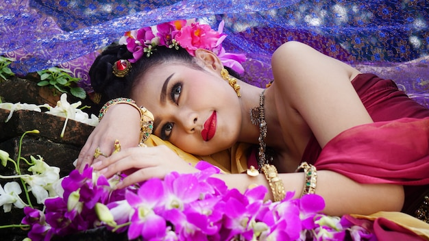 Retrato de mulher asiática bonita de cabelos pretos compridos com traje tradicional de tailândia, deitado por flor
