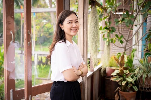 Retrato de mulher asiática bonita na casa do jardim interior