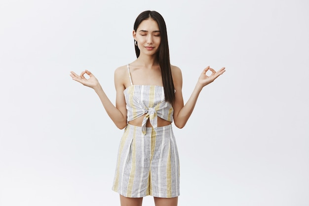 Retrato de mulher asiática calma, relaxada e satisfeita com roupa de verão combinando, segurando as mãos abertas em gesto zen, sorrindo, fechando os olhos enquanto medita ou faz ioga