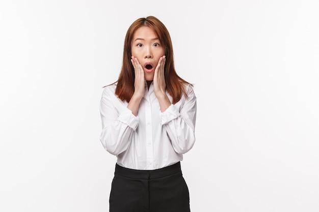 Retrato de mulher asiática chocada e preocupada, encarando com descrença e mandíbula ao ouvir notícias terríveis, não posso acreditar que algo ruim aconteceu, de pé espantado com a parede branca