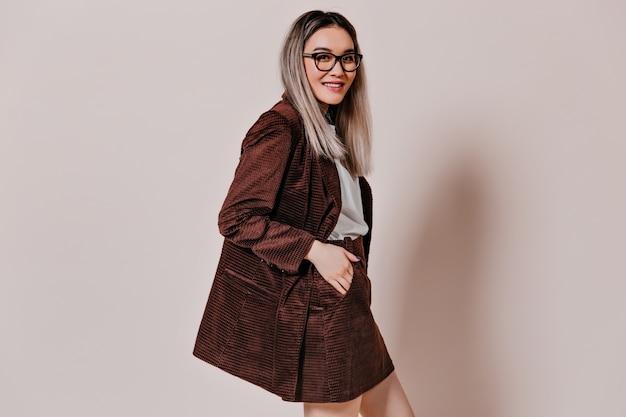 Retrato de mulher asiática com jaqueta marrom em parede isolada