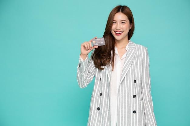 Retrato de mulher asiática de terno segurando cartão de crédito