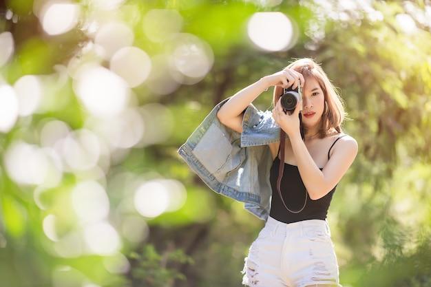 Retrato de mulher asiática é um fotógrafo profissional com câmera mirrorless na mão.