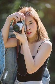 Retrato de mulher asiática é um fotógrafo profissional com câmera mirrorless