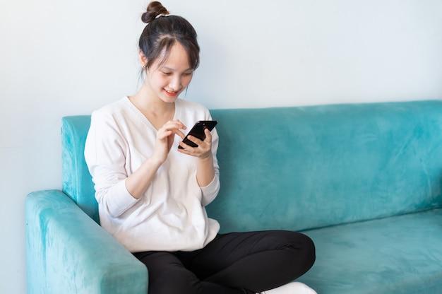 Retrato de mulher asiática em casa, no sofá