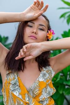 Retrato de mulher asiática em vestido de verão amarelo com flor de plumeria tailandesa no cabelo e brincos redondos