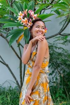Retrato de mulher asiática em vestido de verão amarelo fica com flor de plumeria tailandesa no cabelo e brincos redondos. mulher com luz compõem do lado de fora no fundo da parede e arbustos verdes