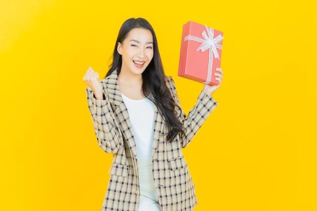 Retrato de mulher asiática jovem e bonita sorrindo com caixa de presente vermelha