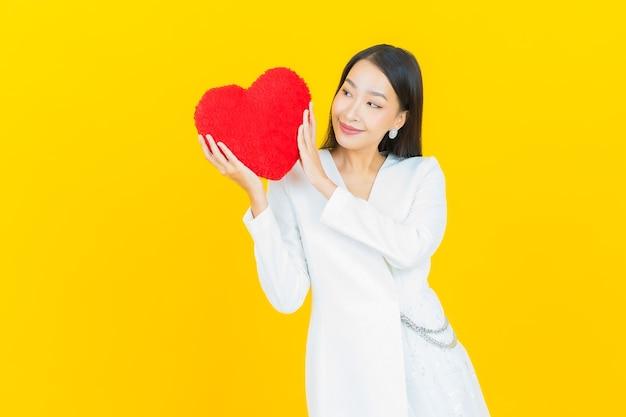 Retrato de mulher asiática jovem e bonita sorrindo com formato de almofada em forma de coração