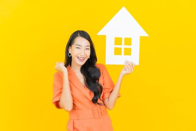 Retrato de mulher asiática jovem e bonita sorrindo com placa de papel de sinal para casa em amarelo.