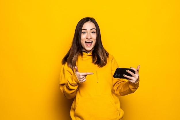 Retrato de mulher asiática jovem e bonita sorrindo feliz usando telefone celular inteligente na parede amarela isolada