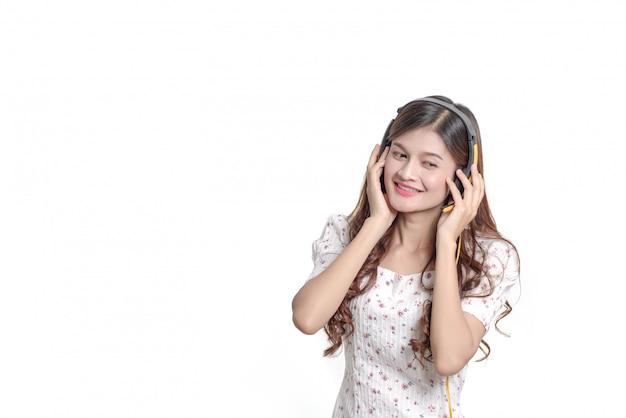 Retrato de mulher asiática jovem feliz colocar fones de ouvido ouve música, linda garota tailandesa sorridente na parede branca