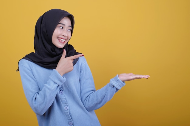 Retrato de mulher asiática linda usando hijab preto, olhando alegremente a expressão apontando e mostrando com o dedo indicador