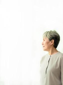 Retrato de mulher asiática madura aposentada pensativa em roupas casuais, em pé perto de uma grande janela.