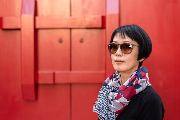 Retrato de mulher asiática moderna contra uma porta de madeira vermelha em um antigo edifício chinês
