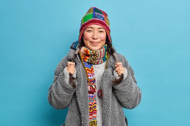 Retrato de mulher asiática segurando dois sorrisos de rabo de cavalo agradavelmente vestida com roupa exterior de malha, chapéu e cachecol no pescoço parece feliz isolado na parede azul