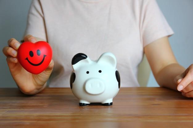 Retrato de mulher asiática segurando um coração vermelho na mão com o cofrinho preto e branco na mesa de madeira, economizando o conceito de dinheiro