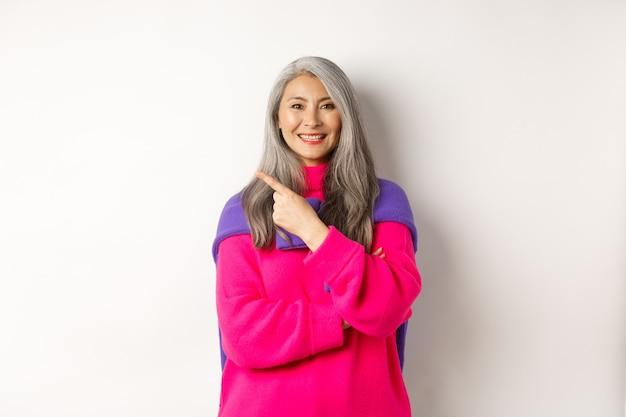 Retrato de mulher asiática sênior feliz sorrindo, apontando para o canto superior esquerdo e parecendo satisfeito, demonstra a promoção especial, em pé sobre um fundo branco.