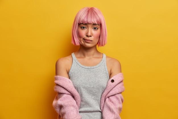Retrato de mulher asiática séria com cabelo rosado, parece entediada, franze os lábios, tem bochechas ruge