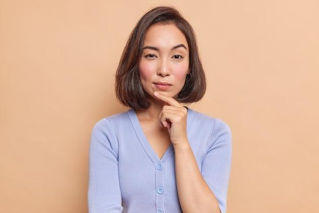 Retrato de mulher asiática séria de cabelos escuros com dedo no queixo e olhar misteriosamente à frente considera algo vestido com blusão azul isolado sobre parede marrom