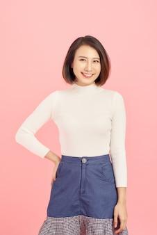 Retrato de mulher asiática sorridente em pé isolado no fundo rosa.