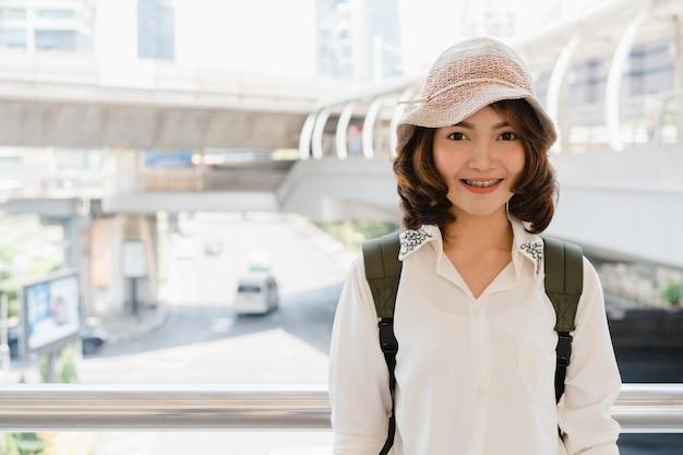 Retrato de mulher asiática sorridente jovem e atraente ao ar livre na cidade