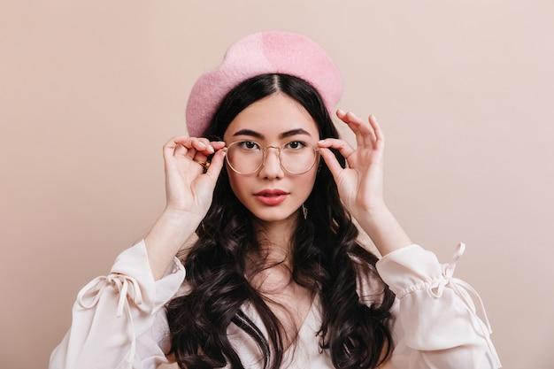 Retrato de mulher asiática tocando óculos. vista frontal do elegante modelo coreano na boina francesa.