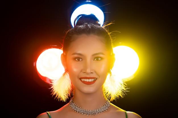Retrato de mulher asiática transgender desgaste verde lindo vestido longo de noite, sorria para a câmera sobre luzes traseiras colorido amarelo, vermelho, borrão com fumaça e poses olhar de moda, iluminação de estúdio cópia espaço