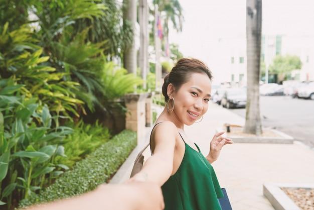 Retrato de mulher asiática, voltando e olhando para a câmera, puxando a mão de seu namorado irreconhecível