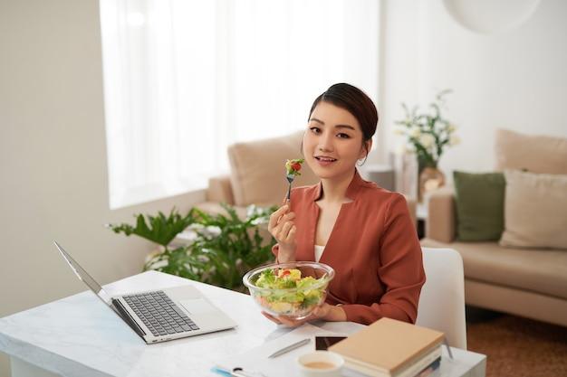 Retrato de mulher assistindo filme no laptop e comendo salada de legumes na mesa no intervalo