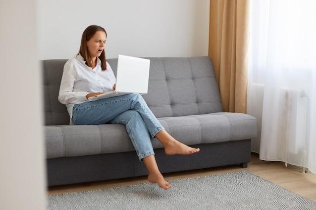 Retrato de mulher assustada de camiseta e calça jeans, sentada no sofá, usando laptop e internet sem fio para trabalhar online, tendo problemas, precisa trabalhar novamente, olhando para a tela com os olhos cheios de medo.