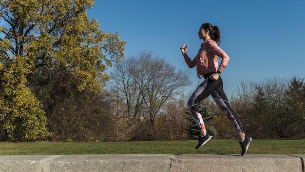 Retrato de mulher ativa correndo ao ar livre