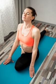 Retrato de mulher ativa, meditando em casa